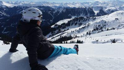 Chłopiec leży na śniegu w górach