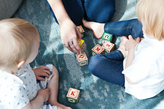 Rodzic bawiązy się klockami z dziećmi